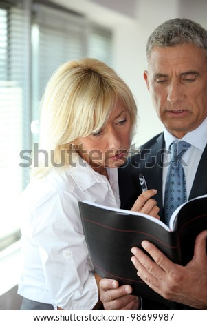 mature businessman consulting his agenda with blonde secretary by his side