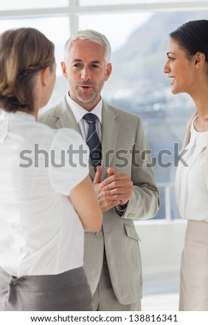 Mature businessman discussing with female colleagues during working hours