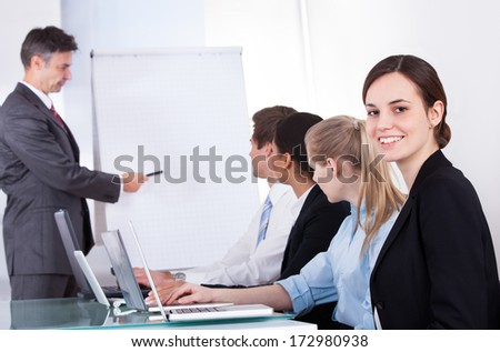 Mature Businessman Giving Presentation To His Colleagues At Office Meeting