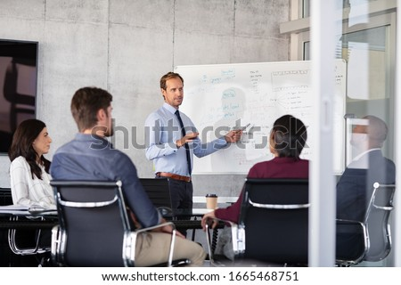Mature businessman giving presentation to his colleagues in modern office. Leader presenting new project to business partners in conference room using white board. Businessman in a meeting talking.