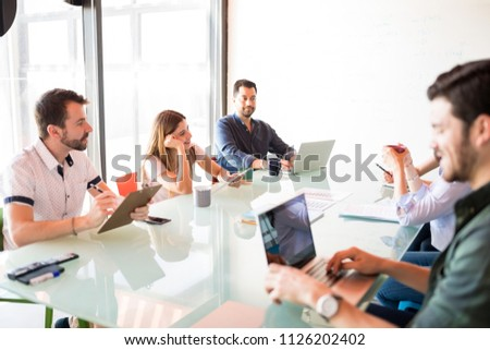Mature businessman holding digital tablet sitting with colleagues and having meeting #1126202402