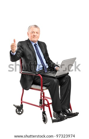 Mature businessman in a wheelchair working on a laptop and giving thumb up isolated on white background