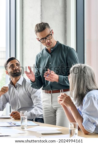 Mature businessman leader mentor talking to diverse colleagues team listening to caucasian ceo. Multicultural professionals project managers group negotiating in boardroom at meeting. Vertical.