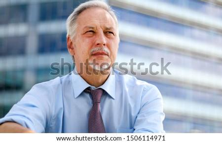 Mature businessman portrait outdoor in  a pensive expression