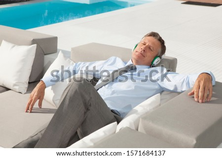 Mature businessman relaxing on sofa with headphones by outdoor pool