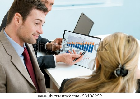 Mature businessman showing growing chart to colleagues in a meeting discussion at office