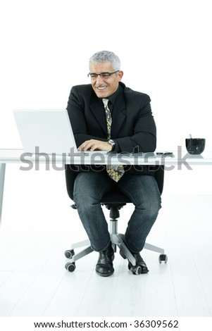 Mature businessman sitting at office desk, working on laptop computer. Isolated on white.