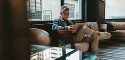 Mature businessman sitting in office lobby with a laptop. Male executive working in office lounge.