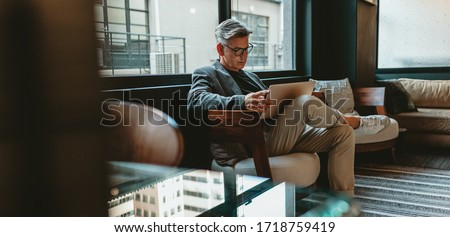 Mature businessman sitting in office lobby with a laptop. Male executive working in office lounge. Сток-фото ©