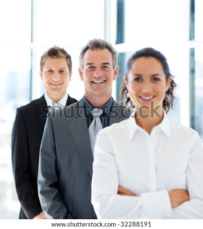 Mature businessman smiling at the camera in a line with his team
