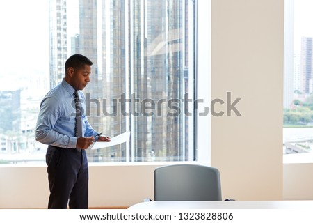 Mature Businessman Standing Rehearsing Before Giving Presentation In Modern Open Plan Office Сток-фото ©