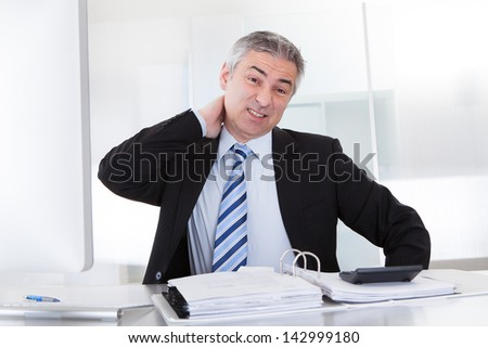 Mature Businessman Suffering From Neck Pain At Office