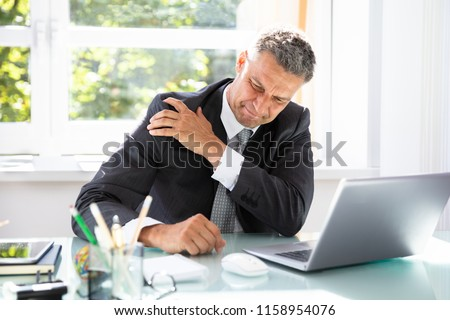 Mature Businessman Suffering From Shoulder Pain At Workplace #1158954076
