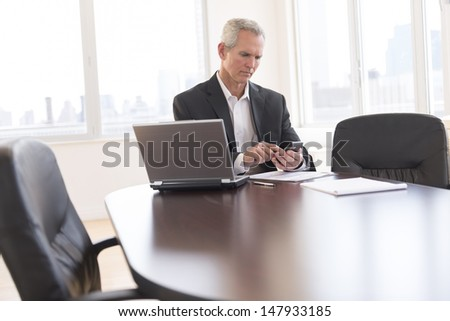 Mature businessman touching smart phone while sitting at desk in office