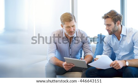Mature businessman using a digital tablet to discuss information with a younger colleague in a modern business lounge