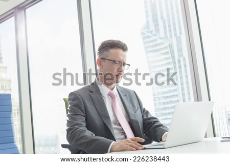 Mature businessman using laptop in office