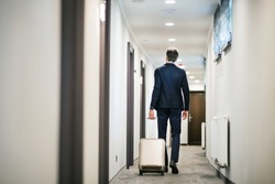 Mature businessman walking with luggage in a hotel corridor.