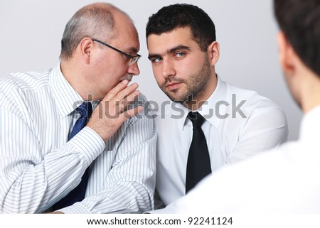 Mature businessman whisper something to his younger colleague during interview, privacy concept
