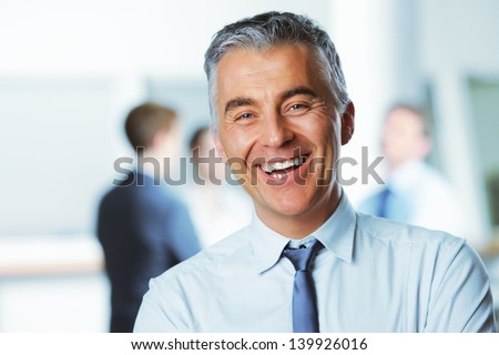 Mature businessman with colleagues in the background #139926016