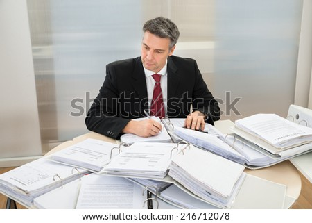 Mature Businessman Working At Office With Heap Of Folders Around Him