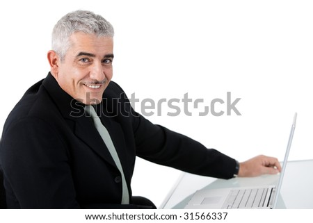 Mature businessman working on laptop computer at office desk, smiling, isolated on white background.