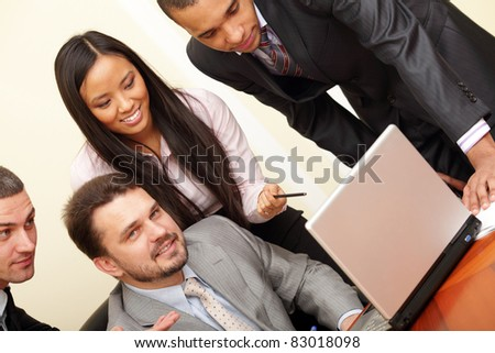 Mature businessman working on laptop with his multi ethnic business team