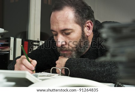 Mature businessman writing on papers at office-overworked at night time. Horizontal shot