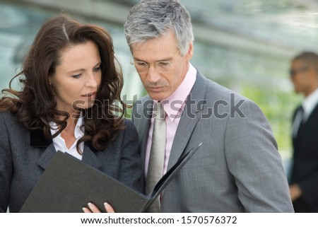 Mature businesswoman and businessman looking at folder #1570576372