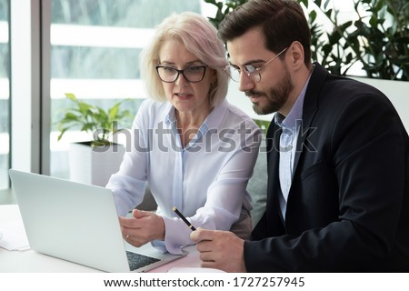 Mature businesswoman and millennial businessman colleagues working together on common project using laptop business application sitting at modern office room. Teamwork, mentoring and coaching concept