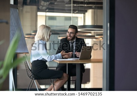 Mature businesswoman and young employee discussing strategy in boardroom with flip chart, manager consulting client, colleagues working on project together, senior mentor teaching new intern