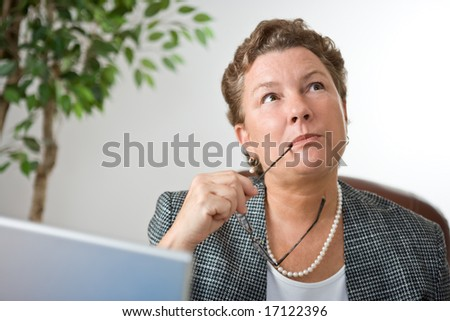 Mature businesswoman at her laptop, gazing into space and thinking.