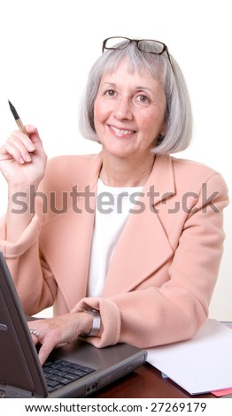 Mature Businesswoman at work in her office. There are several other images in this series. - stock photo