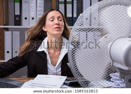 Mature Businesswoman Cooling Herself In Front Of Fan During Hot Weather #1089163853