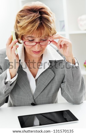 Mature Businesswoman in red eyeglasses talking by phone and working on digital tablet  in the office.