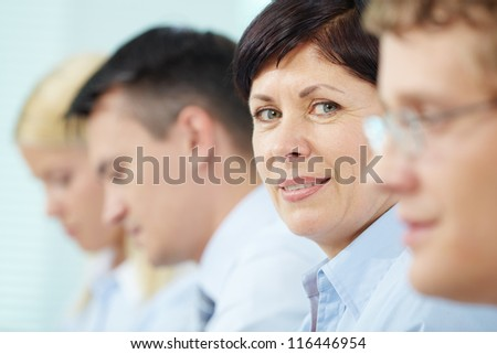 Mature businesswoman looking at camera between her partners