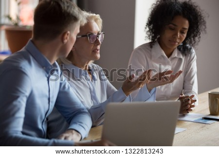 Mature businesswoman sharing ideas with colleagues at company meeting, dissatisfied team leader talking about business strategy, discussing bad project results or business failure at briefing