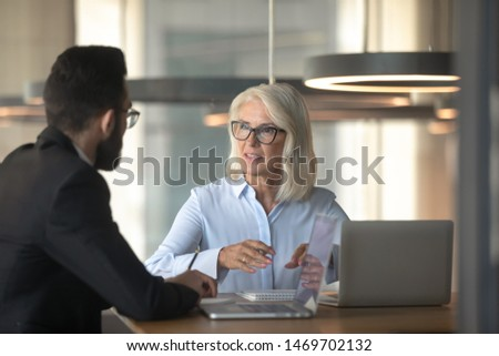 Mature businesswoman talking with business partner in office, senior manager consulting client about loan, insurance, hr holding interview with job applicant, aged mentor training trainee