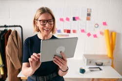 Mature Businesswoman Using Tablet Computer In Studio Of Start Up Fashion Business