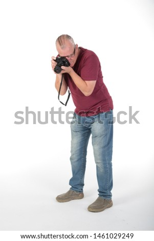 Mature casually dressed male taking photographs with a digital camera. In studio on white background  hobby or pastime