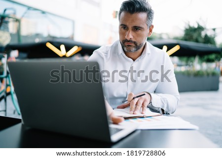 Mature Caucasian corporate director analyzing web information during organisation planning in street cafeteria, middle aged businessman reading news via netbook technology connected to 4g wireless