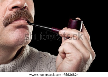 mature caucasian man holding smoking pipe in hand isolated on black background