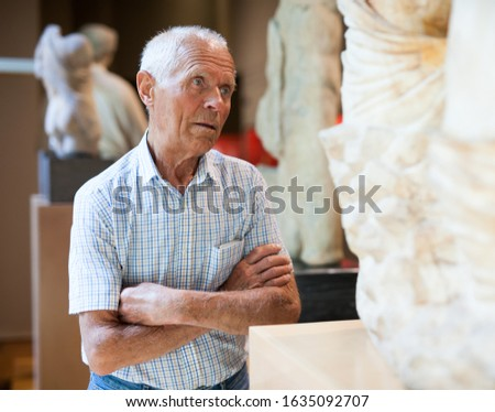 Mature Caucasian man visiting exposition of Art Museum with exhibits of antiquity