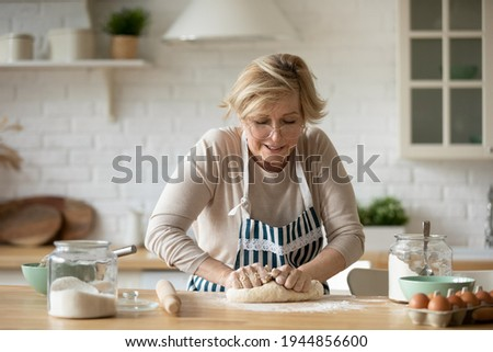 Mature Caucasian 60s woman in apron roll dough baking bread or pie in cozy kitchen at home. Elderly 50s grandmother cooking delicious breakfast, prepare buns pastries or donuts. Culinary concept.