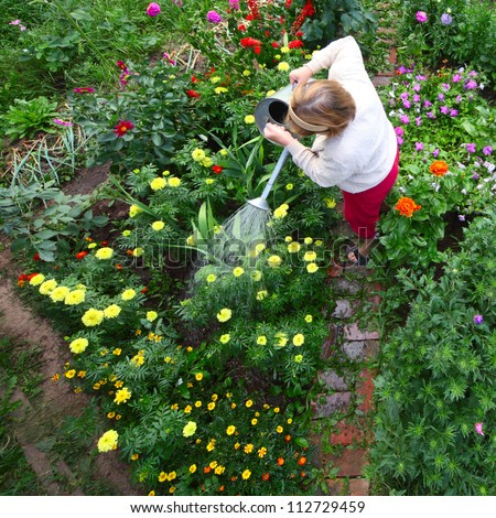 Mature caucasian woman watering her green garden with a lot of flowers