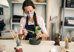 Mature caucasian woman works with ceramics and paints finished cup while wearing protective face mask for coronavirus - Creative cermaic pottery studio