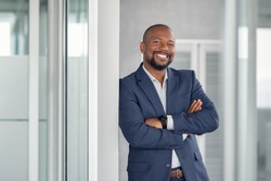 Mature cheerful african american executive businessman at workspace. Portrait of smiling ceo at modern office workplace in suit looking at camera. Happy leader standing in front of company building.