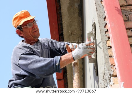 Mature contractor plasterer working outdoors.