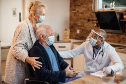 Mature couple and black doctor wearing protective face masks while talking at nursing home.