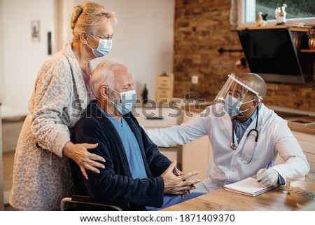 Mature couple and black doctor wearing protective face masks while talking at nursing home. Сток-фото ©