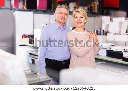 Mature couple are visiting shop of household appliances for survey of goods for kitchen and house.  #1225540225
